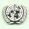 UNITED NATIONS METAL CAP BADGE